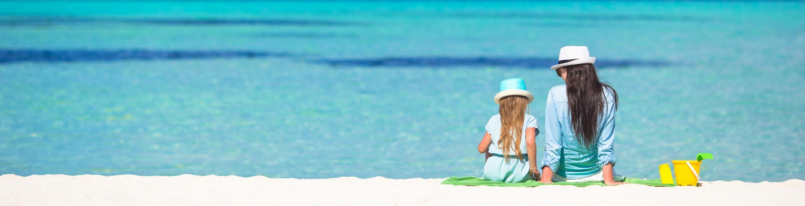 Little girl and young mom relaxing at beach